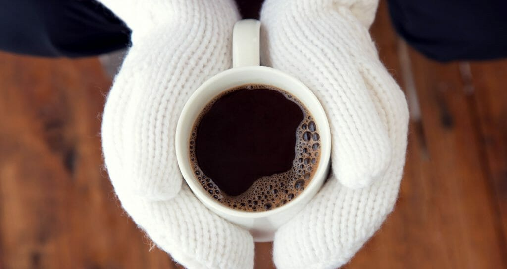 winter sunday morning with coffee in white mittens