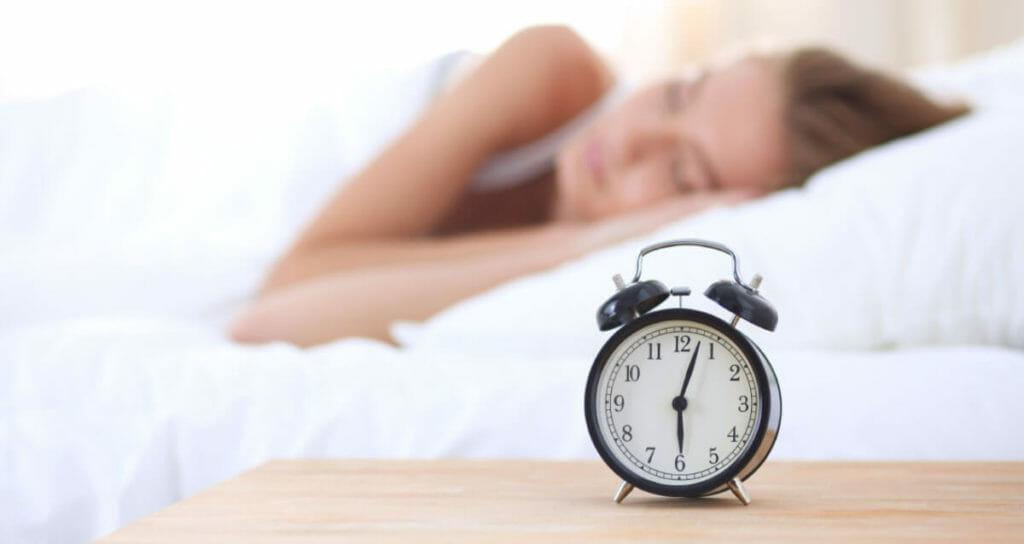 Insomnia Bootcamp Sleeping woman with alarm clock